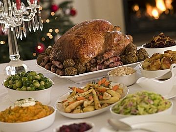 Traditional English Christmas dinner. For most families, recipes for Christmas dinner include roast turkey with all the trimmings - that's sprouts, roast potatoes, carrots, chipolata sausages wrapped in bacon, chestnuts, and bread sauce and cranberry sauce. This is followed by either Christmas pudding or a Christmas trifle and later tea, coffee and mince pies.