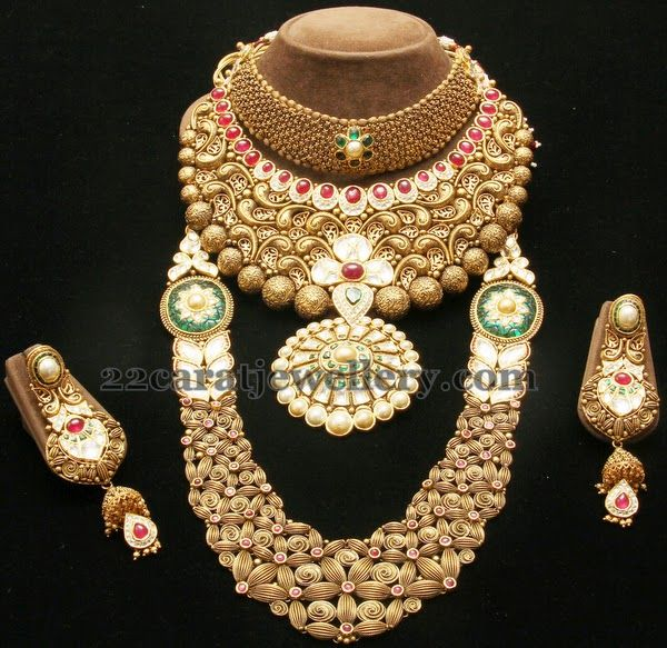 Antique Bridal Jewelry of the Year | Jewellery Designs - Nice machine work broad designer choker in 22 carat gold. Emeralds adorned kundan flower motif decorated on the necklace. Huge antique designer medium size necklace with rubies and polki floral design. Gold round balls edged. Filigree design comes across. Floral patterned nice long chain with broad chain polki floral motifs. It carries matching trendy and classic designer earrings.