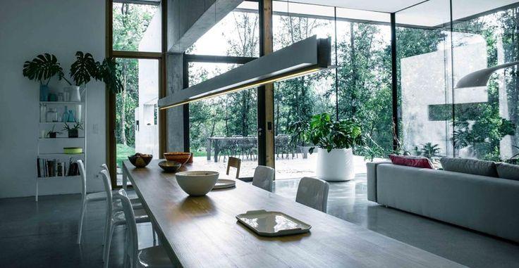 Vivere intorno alla cucina. Sul tavolo da pranzo in legno è sistemata una lunga lampada con ali laterali che si possono utilizzare come piccole mensole. Progetto di Robby Cantarutti e Francesca Petricich.