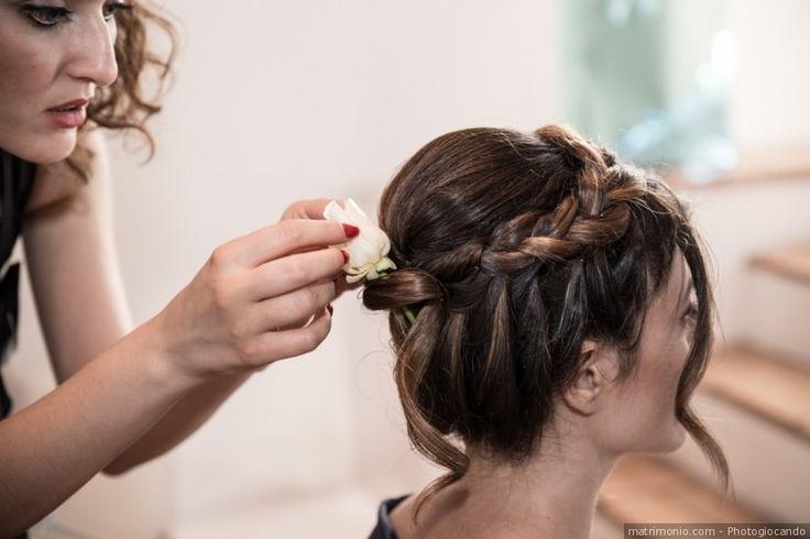Acconciatura da sposa per capelli raccolti in uno chignon alto e treccia con fiori come accessori sposa