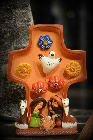 Peruvian Ceramic Cross Nativity  Our Fair Trade Peruvian Ceramic Cross Nativity is so beautiful, you'll want to leave it out all year long. This colorful cross shaped nativity scene depicts the Holy Scene with the Peruvian twist of alpacas. A dove and flowers also join the Nativity Scene.  Handmade by artisans in Peru who are able to support their families through their work with Fair Trade.