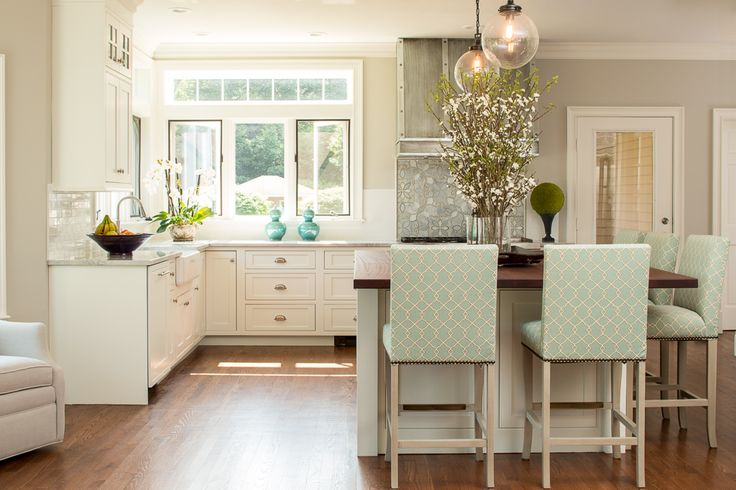 Splashes of turquoise inspire fun and bring a vibrant feel to this hilltop Yarmouth, Maine, home. Corner windows allow the sun to warm the bright colors inside. Fresh, white cabinetry and wood countertops balance one another out. And industrial touches like the weathered range hood pair with the classic trellised chair patterns seen on the island barstools, lending the home a unique and balanced personality. A true modern statement with a classic touch.