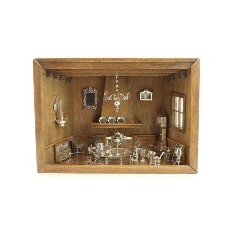 Een toonkamertje met diverse miniaturen Het interieur bestaande uit een openhaard, 3 wandbordjes, een secretaire, een staande klok, een piano met krukje, 3 diverse kannen, twee kandelaars, een spiegel, fotolijst, vogelkooi, olielamp, theestoof, voetenstoof, haardketel, tafel, bankje, twee stoelen, een bolkroon, haardstel en kolenkit en nog twee miniaturen van figuren. Z. 835. Meest 20ste eeuw.