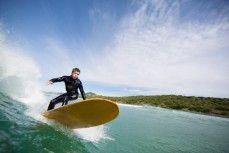 Local surfboard shaper Skep rides a longboard at Blackhead Beach, Dunedin, New Zealand.