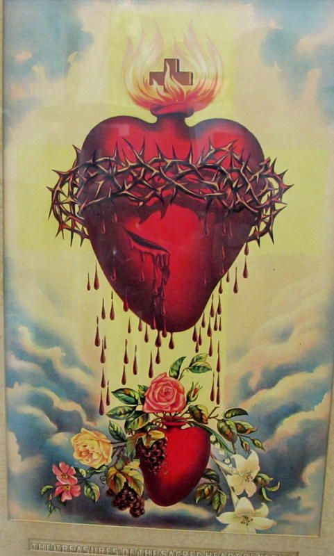 The Sacred Heart is shown wounded, encircled by a crown of thorns, surmounted by a Cross, and aflame with love for mankind.  Corazon ardiente de Jesus Hijo de Maria Santisima.   Read more about this devotion at FishEaters.com