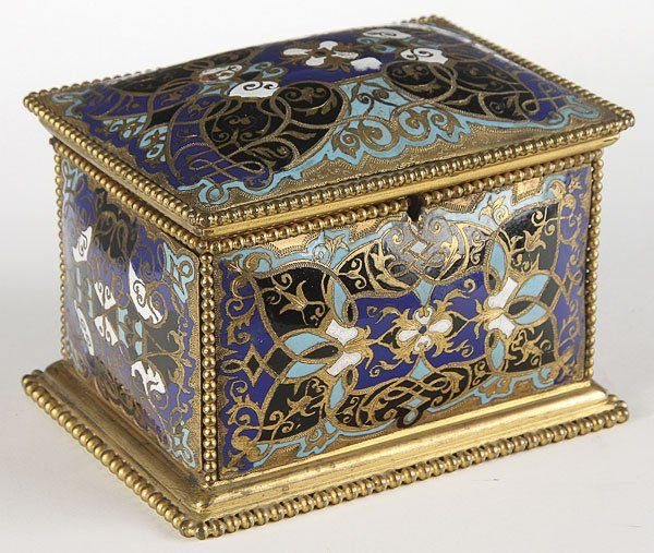 A FINE FRENCH CHAMPLEVÉ ENAMELED AND GILT BRONZE LIDDED CASKET, 19TH CENTURY. Of rectangular form with convex panels in an Arabesque design, the interior with a diamond quilted silk satin lining.