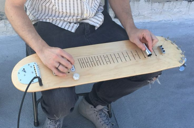A Cleverly Designed Functioning Steel Guitar That's Built Onto a Blank Skateboard Deck