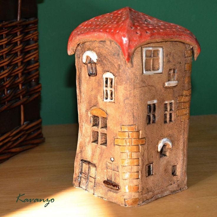 Věžička Keramická věžička - domek na svíčku. Průřezy v některých okýnkách vytvářejí iluzi svítícího domečku. Šamotová hlína, burel, bílá a červená glazura. Výška 21 cm, průměr 11 cm.