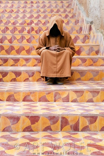 Africa | A hooded man sits on colorful steps, Essaouira, Morocco |  © Art Wolfe