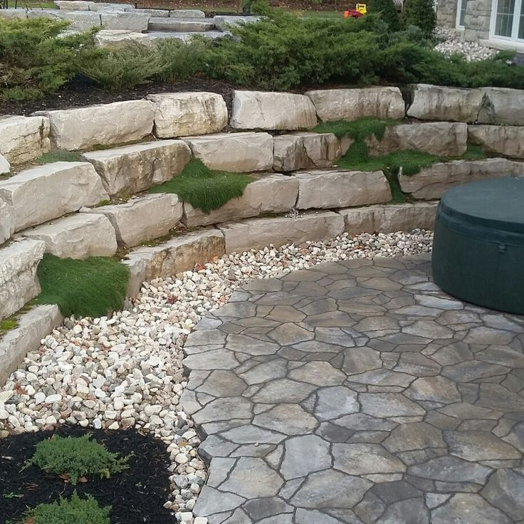 Walkout basement patio,hot tub,precast pavers,Permacon mega arbel, armour rock wall ,plants,river rock.