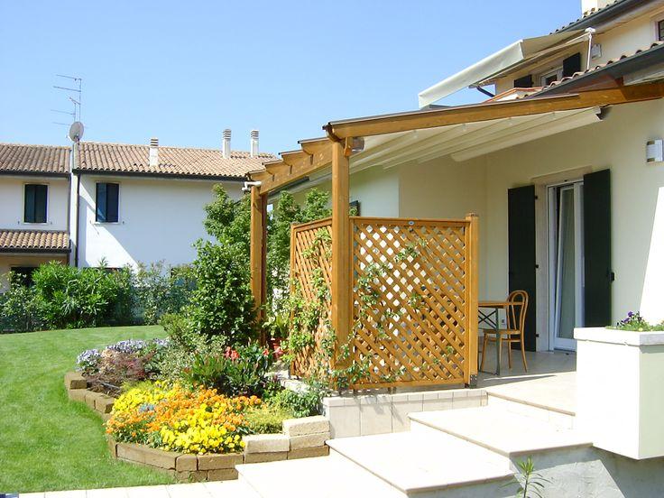 Pergola in legno lamellare con tenda scorrevole ed impermeabile in pvc. Pannelli grigliati a maglia fitta a schermare il tavolo da giardino.
