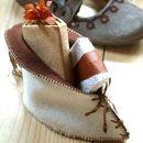 Nodig:ecru en bruin vilt * bruin suède koord * bruin borduurgaren * houten kraaltjes : de lengtedoormeter van het zooltje moet ongeveer 10 cm zijn) en knip het uit . Leg het patroon op vilt en knip 1 ecru en 1 bruine schoen + 1 ecru en 1 bruine zool. Leg de ecru en de bruine zool op elkaar. Speld de zool aan de ecru en aan de bruine schoen (ecru aan de buitenkant) en naai rondom met een festonsteek vast.Aan rechterschoenhelft, langs de voorrand, 6 gaatjes op 1 cm van elkaar.