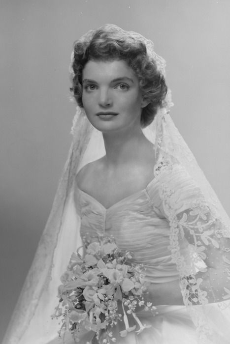 Bridal portrait of Jacqueline Lee Bouvier (1929 - 1994) shows her in an Anne Lowe-designed wedding dress, a bouquet of flowers in her hands, New York, New York, 1953. © Bachrach/Getty Images