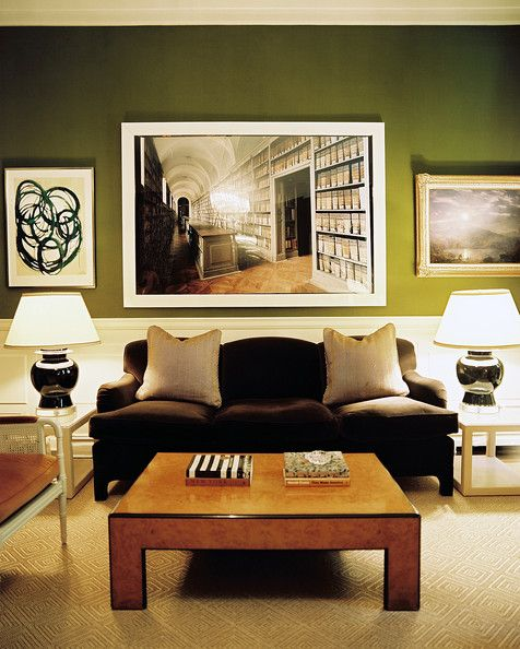 Living Room Photo - A brown couch in front of green walls covered with art