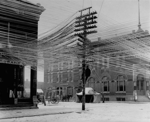 1911: View of a lineman working on power or telephone lines at an intersection in Pratt, Kansas. Various offices and storefronts are apparent in the background. Wow - That's a large amount of lines!