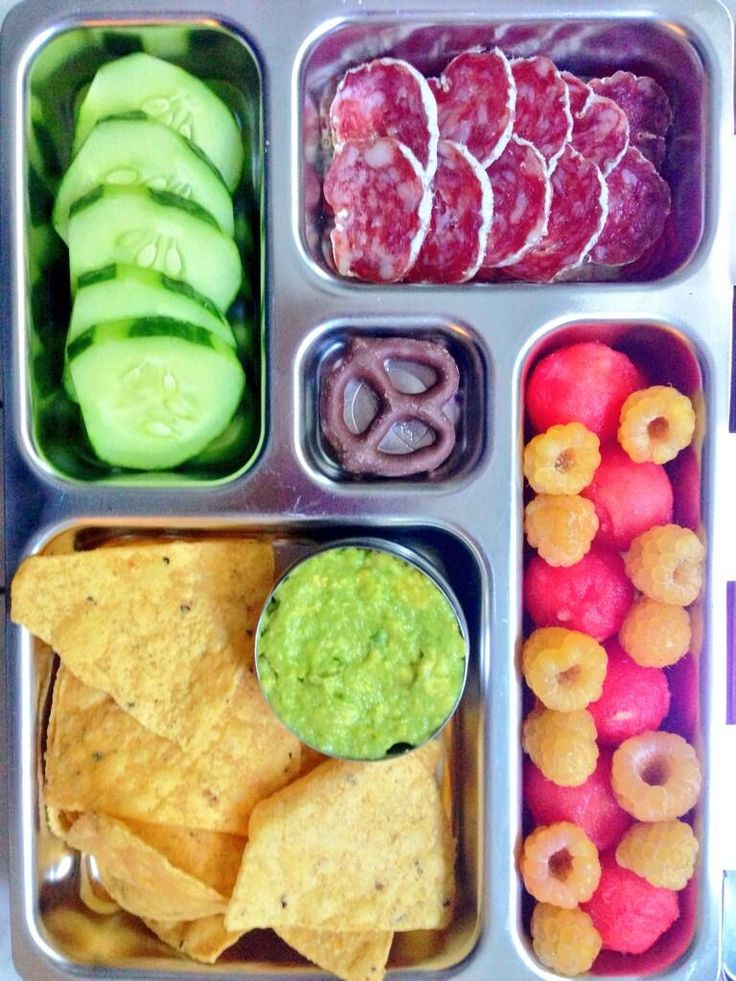 Baked corn chips with guacamole, raspberries, chocolate covered pretzel, cucumbers, salami.