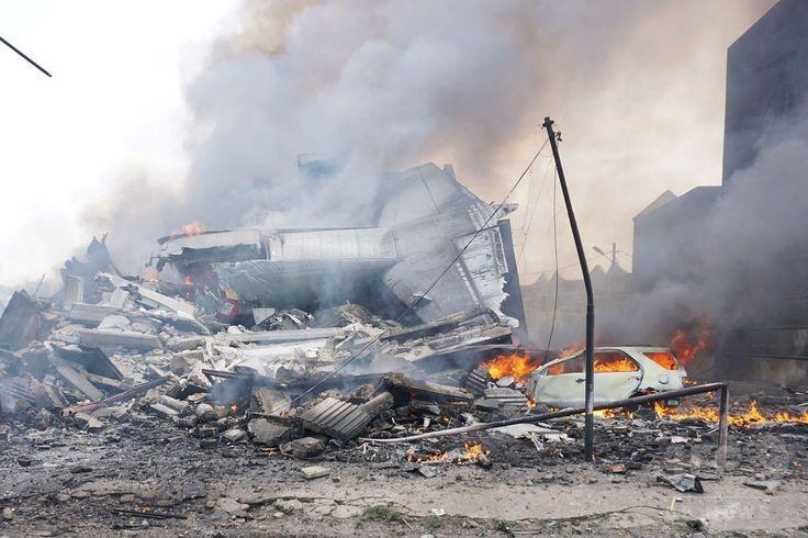インドネシア・スマトラ島メダンで、墜落・炎上した空軍輸送機の尾翼部分(2015年6月30日撮影)。(c)AFP/MUHAMMAD ZULFAN DALIMUNTHE ▼1Jul2015AFP|インドネシア軍機墜落、死者141人に http://www.afpbb.com/articles/-/3053313