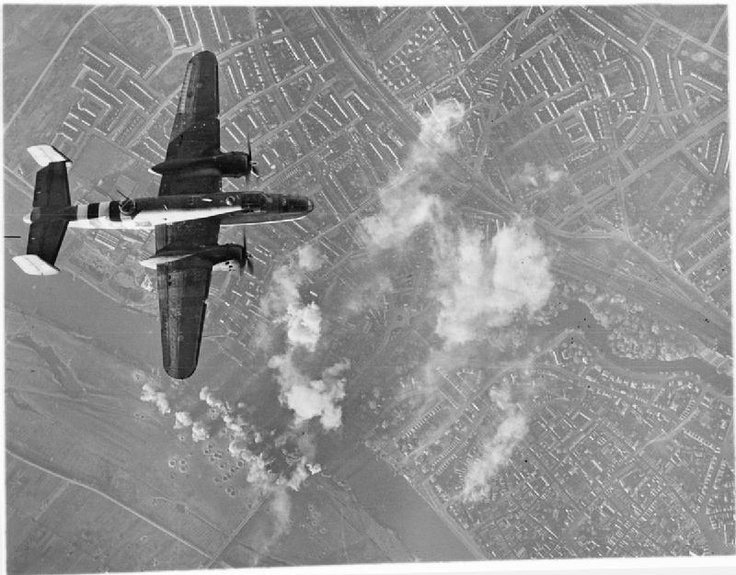 A North American Mitchell Mark II of No. 180 Squadron RAF flying over the target during a daylight attack on the railway bridge over the River IJssel at Deventer, The Netherlands.