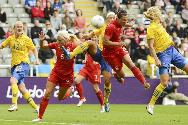 Canada's Melissa Tancredi (C-14) heads the ball in for Canada's second goal past Sweden in their women's Group F football match at the London 2012 Olympic Games at St James' Park in Newcastle, northern England July 31, 2012. REUTERS/Nigel Roddis (BRITAIN - Tags: SPORT OLYMPICS SPORT SOCCER)