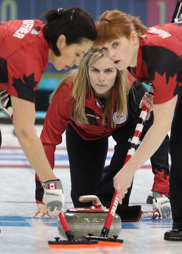 Team Canada's skip Jennifer Jones of Winnipeg, MB (C) delivers a shot as Canada's second Jill Officer (L) and first Dawn McEwen sweep during their women's curling round robin game against Britain at the 2014 Winter Olympics in Sochi, Russia, on Wednesday February 12, 2014