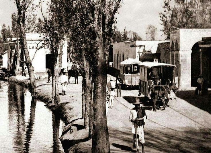 """Imagen donde se aprecia el Canal de la Viga a su paso por el pueblo de Iztacalco. Un par de tranvías de mulitas viajan por la calle de Zapotla; del lado izquierdo se encuentra la forrajería """"La esperanza"""", inmueble que sobrevive hasta la actualidad. El canal desapareció a esta altura en la década de los cincuenta y su trazo se convirtió en la Calzada de la Viga. ca. 1900"""