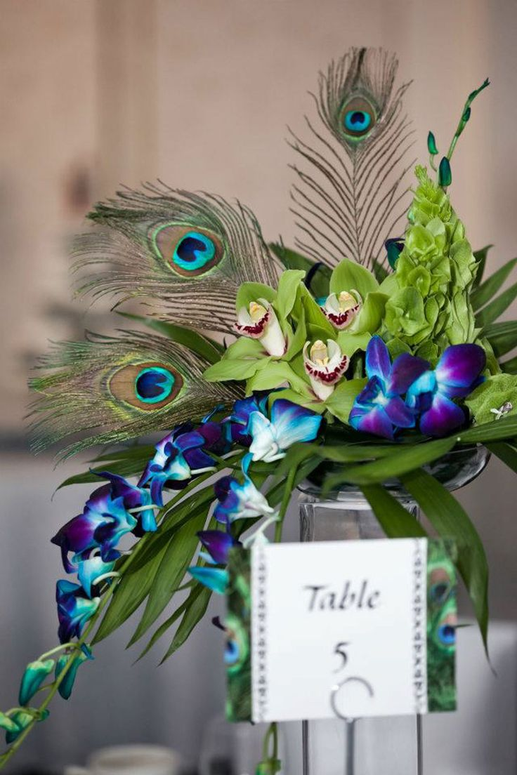 Peacock themed wedding centre piece! I like the draping flowers with the