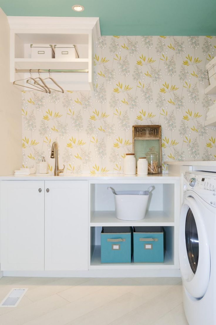 As seen on Love It or List It, Too, once a family room with dark wood paneled walls, this new laundry room fulfilled Kelly's request for a proper laundry room with storage. Her previous closet laundry room off the kitchen was too small for modern appliances and did not have space for folding or storage. The foxglove wallpaper was part of the Scandinavian feel of the overall renovation design.