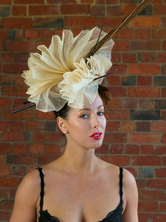 CHAMPAGNE TIFFANY   Hat/Fascinator for Caulfield Cup   FORD MILLINERY  $420  Hand-pleated vanilla sinamay, sculpted into one continuous double-fan that claims height and delicately touches the face. One ostrich quill spine orbits the centre, as the other stands tall fore contrast. Two glorious golden tail pheasant feathers (70-80cm) add even more height. Elegant, refined, and naturally glamourous.