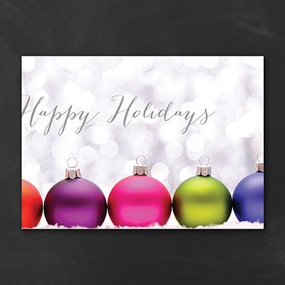 Spark some holiday excitement with your Christmas card! Bright white lights sparkle behind brightly colored ornaments on a sparkling white background.     Made from recycled paper by manufacturers using renewable energy sources.