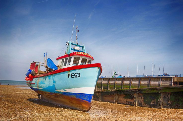 Whitstable, Whitstable, England - Colourful fishing boat sitting on the beach at Whitstable harbour. If you enjoy seafood its a great place to visit with a number of restaurants located on the seafront.