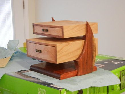 """Cantilever Jewelry Box - """"This is an elm jewelry box I just finished. It is elm, rosewood sides, and a jatoba base. It's based on the Cantilever Box that was in Wood Magazine a few issues back. I just increased the size to handle two boxes instead of one. It's finished in tung oil. The sides are made to resemble a sail. The biggest headache with this one was sanding down the elm to make the rounded front. I'd forgotten how hard elm can be."""""""