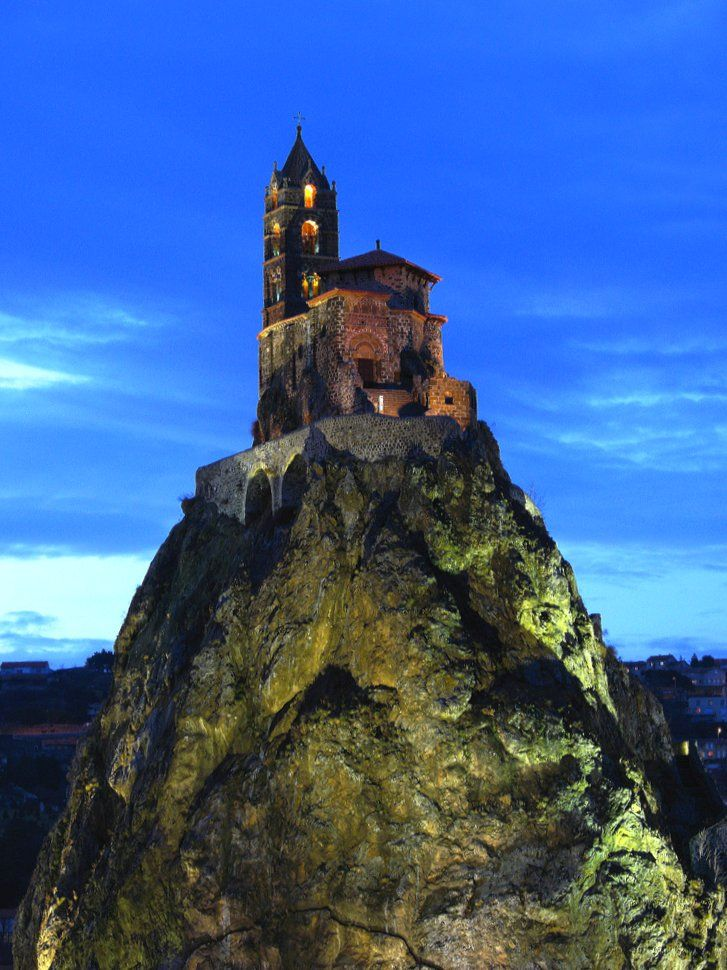"""""""Saint Michel d'Aiguilhe in Le Puy en Velay , Southern France seems to grow out of the rock it was built on in the 10th century. The steep climb – 268 steps to the top, 85 metres (280 ft) up – did not deter pilgrims then and likewise doesn't deter visitors now. The history of this well-preserved church is fascinating and the views are simply stunning."""""""