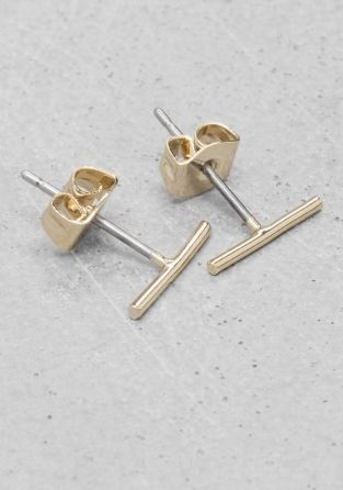 Simple and discreet, these thin bar studs are made from shiny brass. via &otherstories