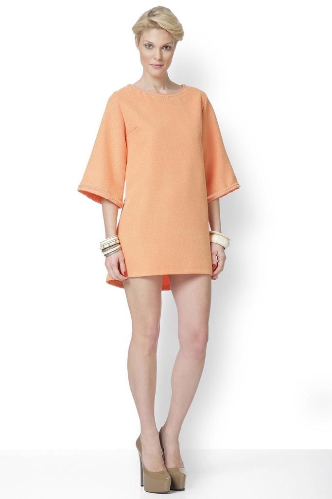 Φόρεμα μίνι σε γραμμή άλφα. Δεν έχει φερμουάρ, ούτε φόδρα και στολίζεται με τρέσα ίδιας απόχρωσης στο λαιμό και τα μανίκια.