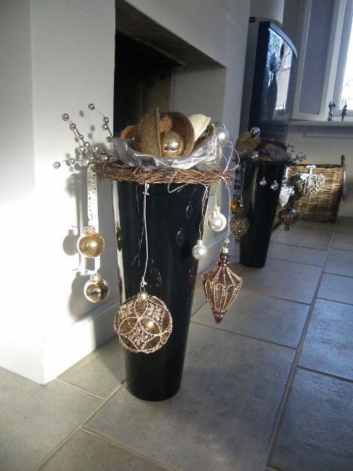 Kerst - op n zwarte vaas een ring gelegd en daarop wat kerstballen en voile. Aan de ring ook hangende kerstversiering. twee dezelfde potten aan beide zijden van de open haard.