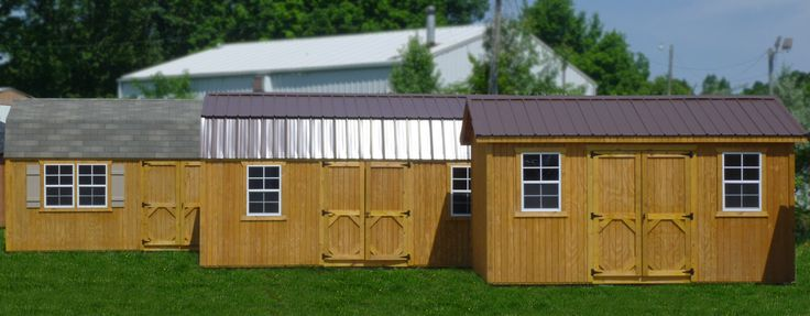 Three pressure treated wooden storage buildings with grass.