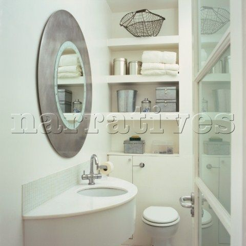 small bathroom with built in storage decorated in white with a large