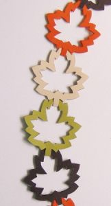 Autumn-hued folded paper leaves are linked together to create a garland. Make a leaf and center leaf template from a piece of cardstock. Fold 11 x 6 inch piece of paper in half crosswise. Place the leaf template on the folded edge of paper.