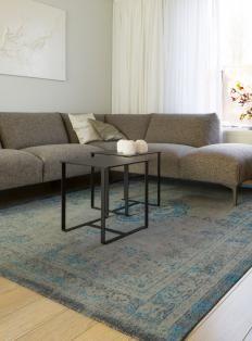 Kleine ruimte; gebruik grote meubels. 1 mooie bank en een kleed om de ruimte te defineren..