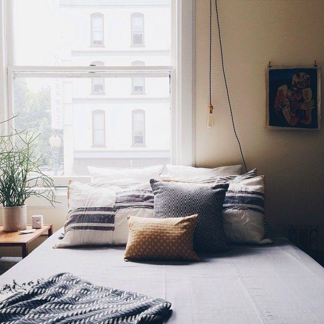 Bedroom // hanging lightbulb // neutral blues // indoor plant // home decor