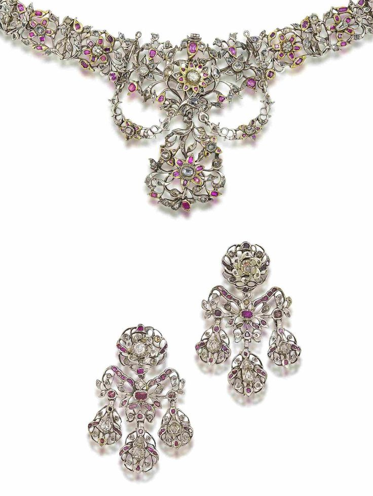A ruby and diamond necklace and earring suite, circa 1770  The necklace designed as a highly stylised openwork band of floral and foliate motifs, set throughout with vari-cut diamonds and rubies, suspending an esclavage motif, accompanied by a pair of similarly-set girandole earrings, all stones in foiled closed-back silver settings, convertible to a tiara, later frame supplied, earring length 6.5cm, fitted case