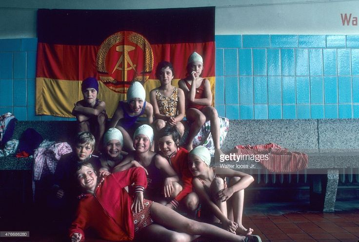 Portrait of youth athletes posing in front of East Germany flag during photo shoot outside pool. East Germany 6/7/1976