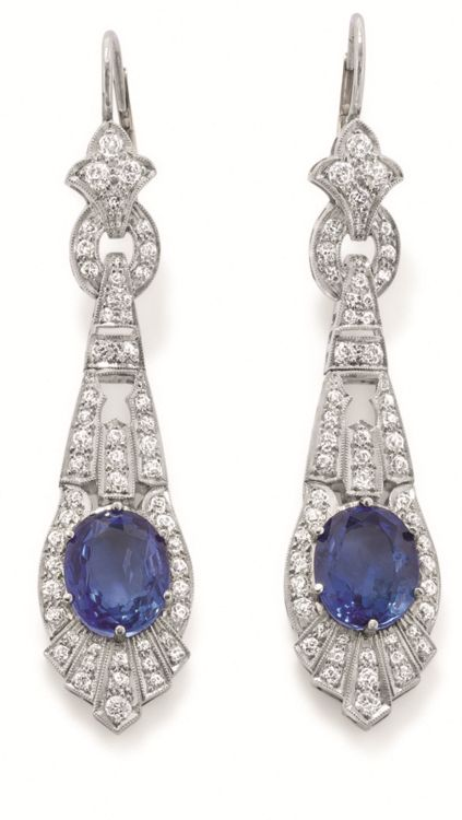 A Pair of Art Deco Sapphire and Diamond Ear Pendants. Each designed as an openwork, articulated pendant drop, set with an oval-cut sapphire, weighing approximately 8.00 carats total, mounted in platinum, length 2 1/2 inches. Via Doyle New York.
