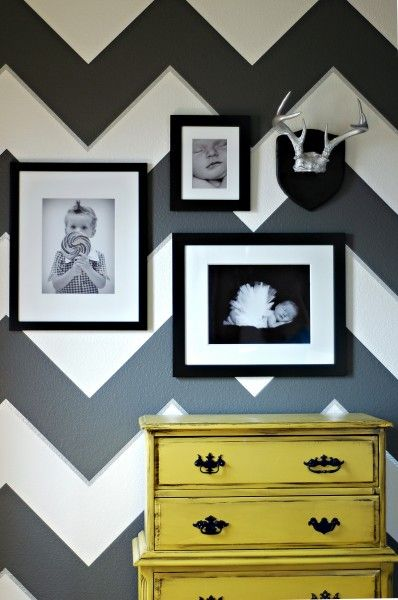 Chevron walls, yellow dresser, silver antlers, frames.