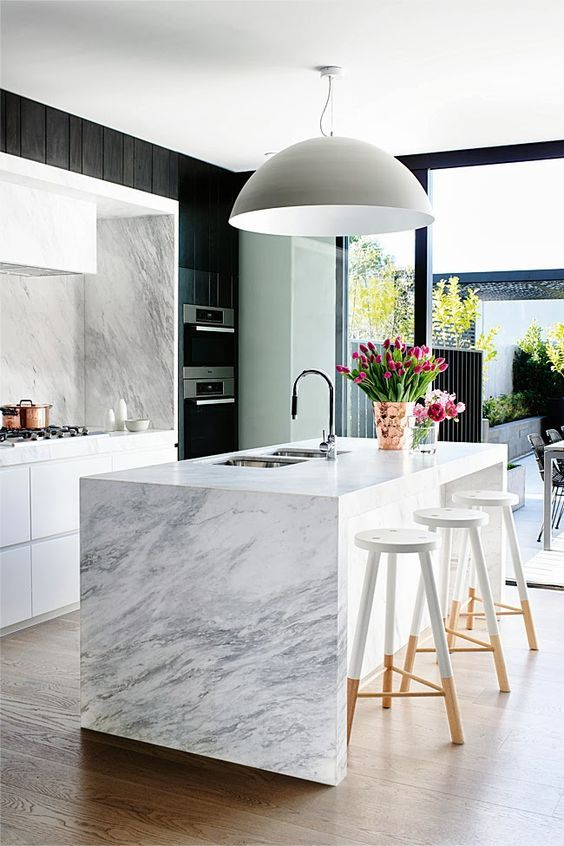Modern marble kitchen dark feature cabinets but there is a lot of natural light