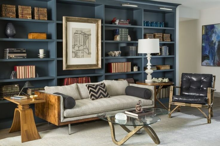 The formal living room has the same balance of masculine and feminine, particularly in the deep blue bookshelves matched with the more elegant glass-topped walnut coffee table and a vintage lamp from the 60s.