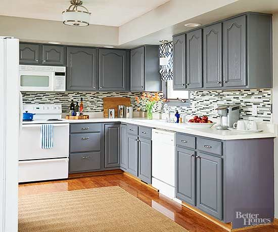 Coats of gray paint refresh and update stock cabinetry. The backsplash tiles in this gray kitchen pull together the colors of the cabinets, countertops, walls, fixtures, and hardware for a comprehensive composition that contributes a sense of unity and pumped-up pattern./