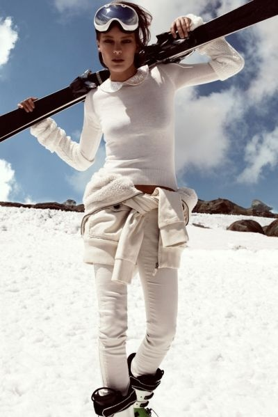 Skiing outfit: skiis, poles, snow boots, ski boots, ski mask, slim fitting snow pants, thermal underwear, thick socks, colored shirt under pullover, zip up ski jacket, and snow gloves.