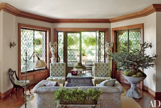 Diamond-pattern French doors and windows are a highlight of the living room; the antique button-tufted chairs, from Liz O'Brien, are grouped with a sofa clad in a Groves Bros. Fabrics cotton and a blue spruce planted in a vintage faux-obis birdbath | archdigest.com