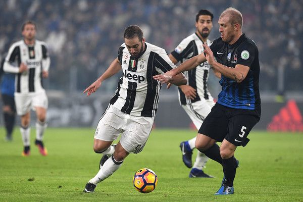 Gonzalo Higuain (L) of Juventus FC is challenged by Andrea Masiello of Atalanta BC during the Serie A match between Juventus FC and Atalanta BC at Juventus Stadium on December 3, 2016 in Turin, Italy.